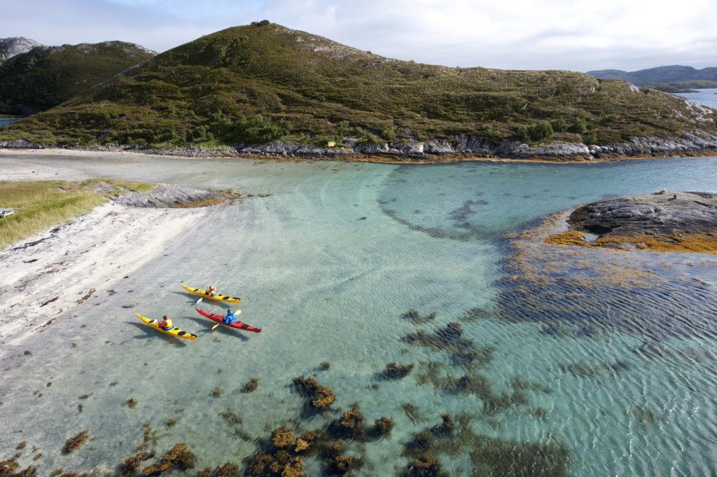 Tre kajakker i blå-grønt vann rett ved en sandstrand på Rødøya på Helgelandskysten. Foto: Terje Rakke.