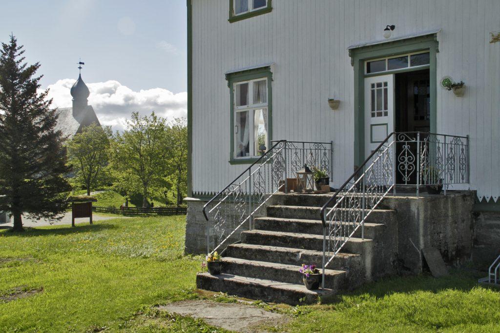 Inngangsparti med trapp inn Dønnes Gård. I bakgrunnen til venstre mellom trær står Dønnes kirke.