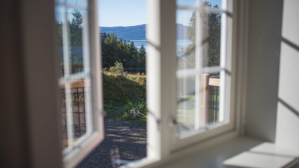 Utsikt fra åpent vindu i rom mot skog, fjord og fjell
