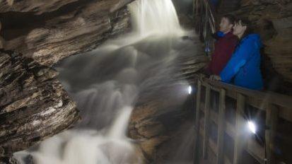 To personer på ei bro med foss inne i grotta