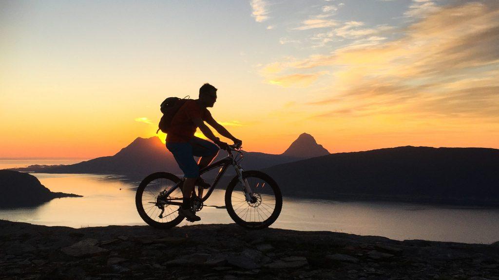 Syklist på fjellet i midnattsol