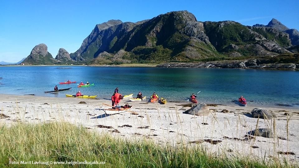 Kajakkpadlere på sandstrand på Tomma