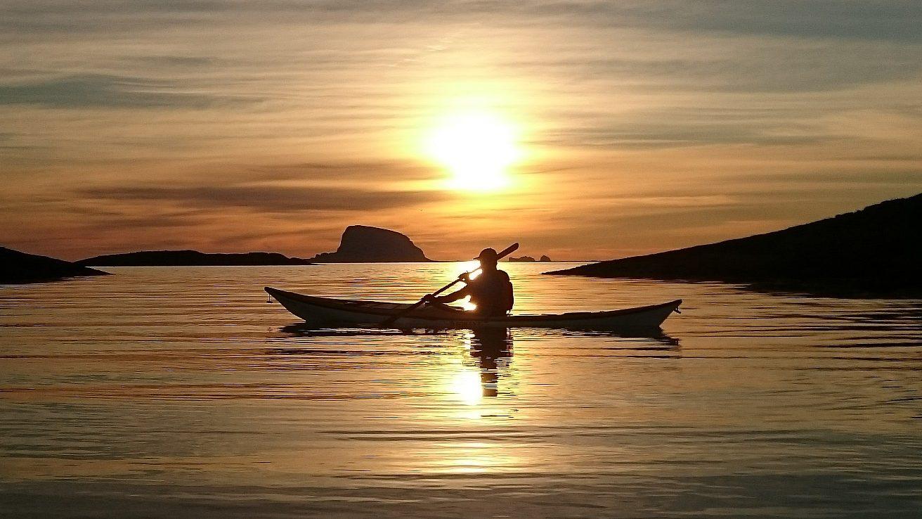 Kajakkpadler i kveldssol med Lovund og Træna i horisonten