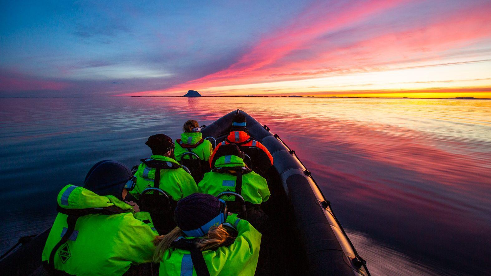 Rib med passasjerer på tur i solnedgang