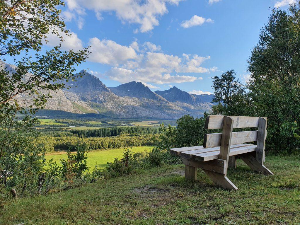 Utsikt mot fjellkjeden De Syv Søstre sett fra en sittebenk i naturen en solskinnsdag