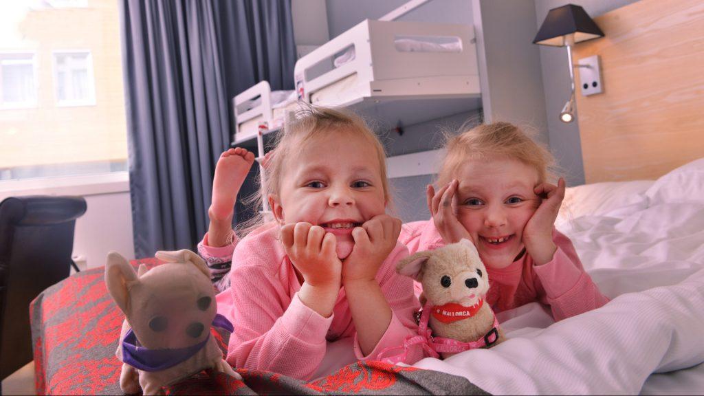 Barn som ligger i senga med kosebamser på et familierom