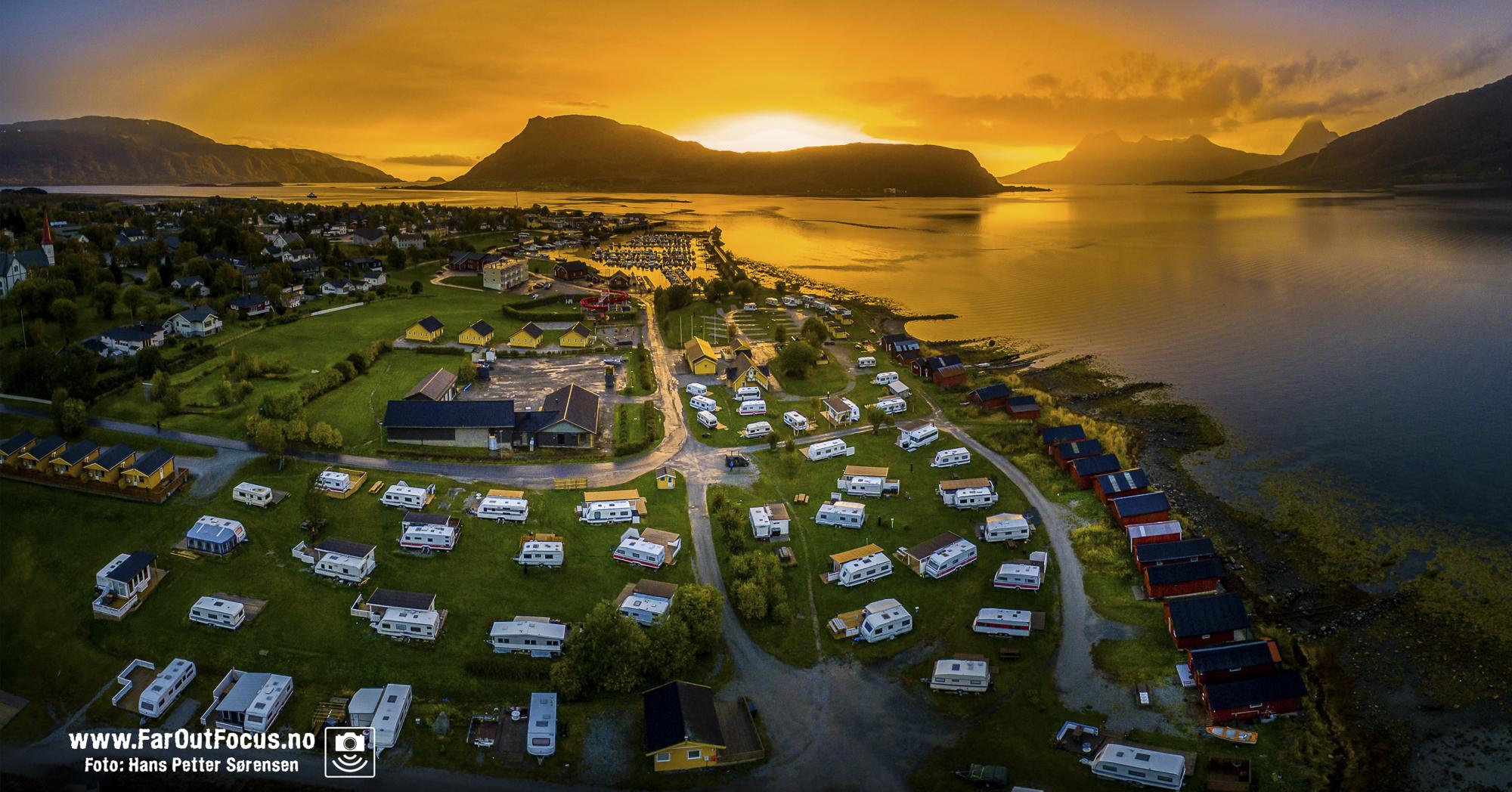 Campingplassen Havblikk Camping på Nesna sett fra lufta, med bobiler, campingvogner og campinghytter. I bakgrunnen går sola ned bak øya Hugla, og vi ser fjellene på Tomma bak til høyre. Foto: Hans Petter Sørensen.