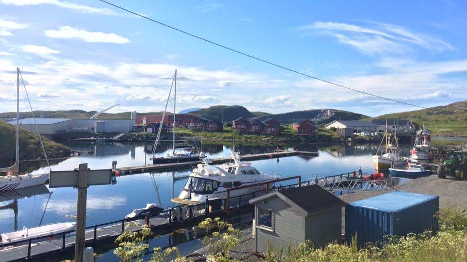 Utsikt mot havn med fiskebåter og Sanna med Trænstaven