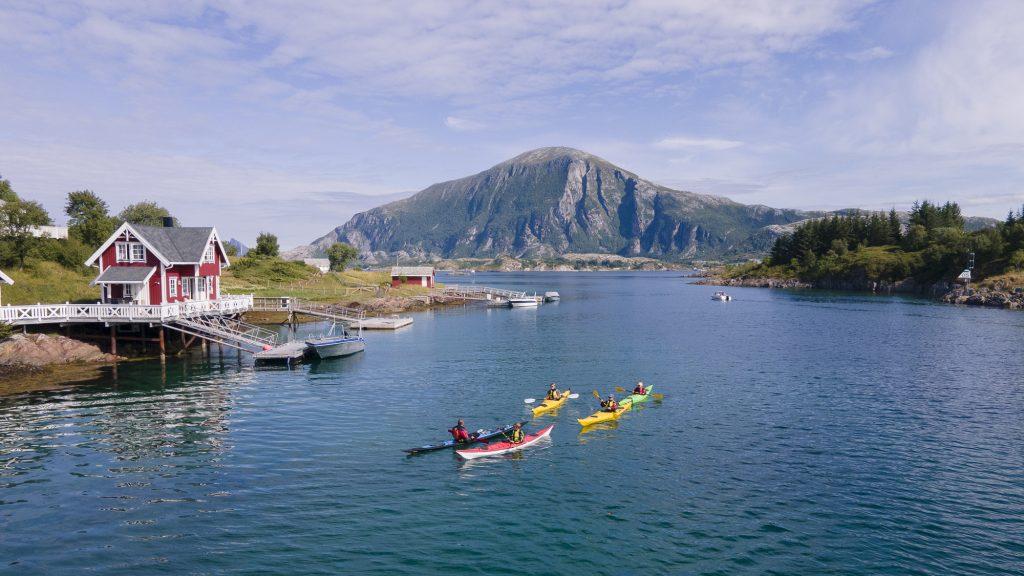 Familie på fire på guidet kajakktur på vei gjennom et sund med guide. I bakgrunnen ser vi båter og Lurøyfjellet, og til venstre et bryggehus.