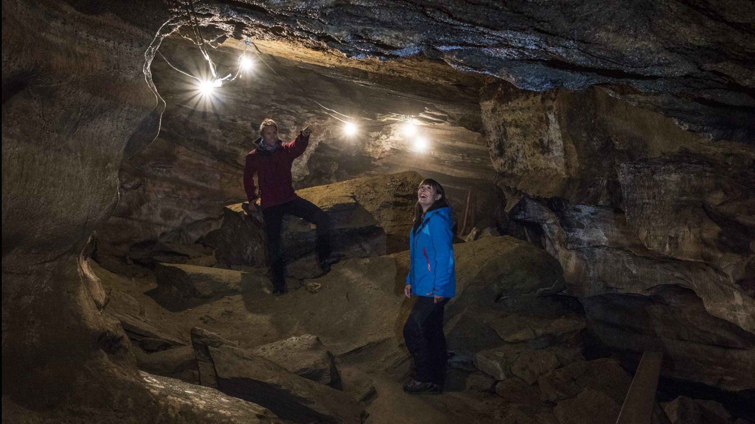 Mann og kvinne som kikker seg om og ler inne i Grønligrotta