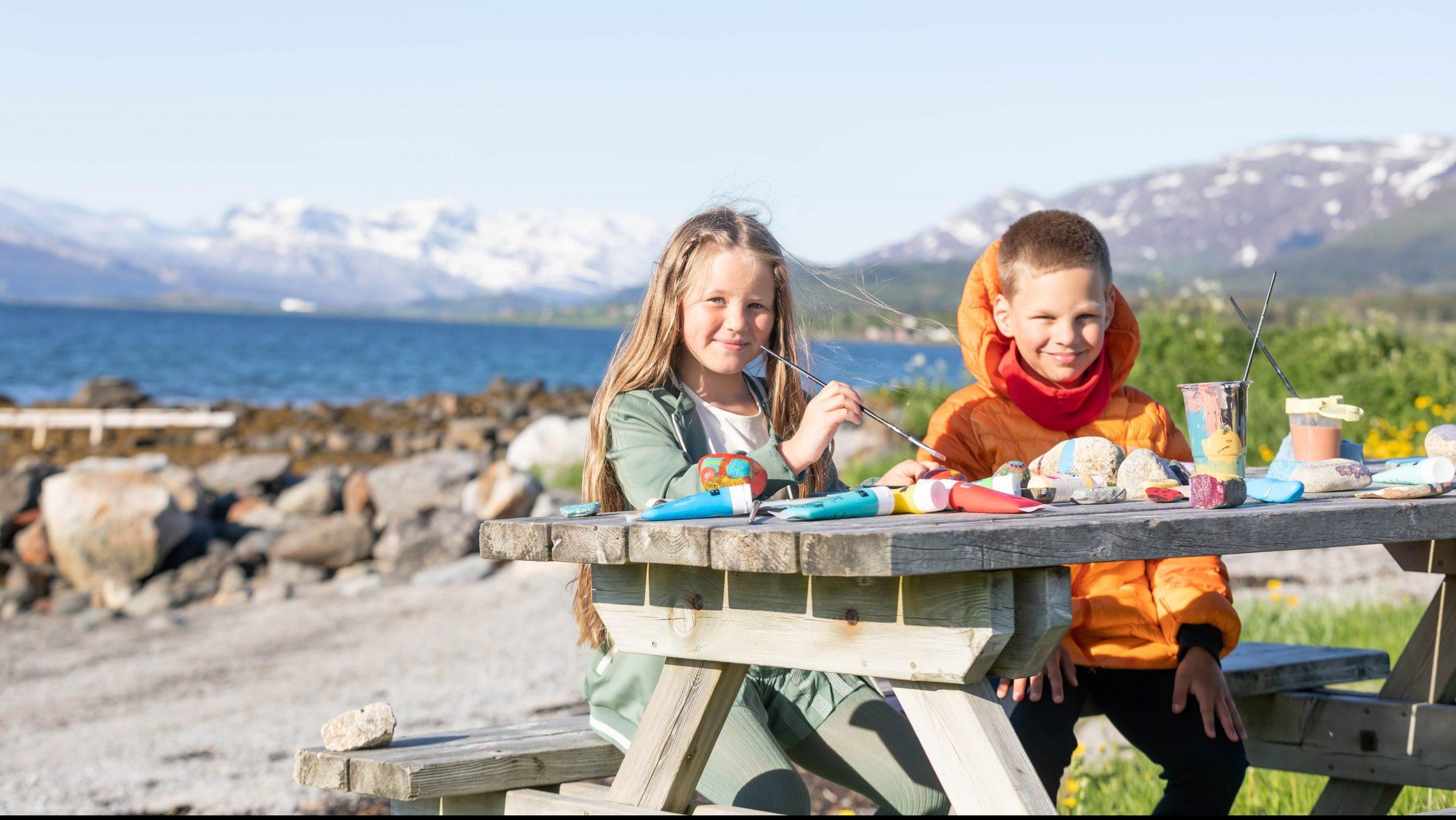 To barn som sitter ved et bord ved fjæra og maler på stein