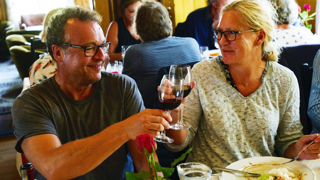 Smilende par som skåler ved matbordet på spisestuen i Dønnes Gård, med velkomststua i bakgrunnen til venstre