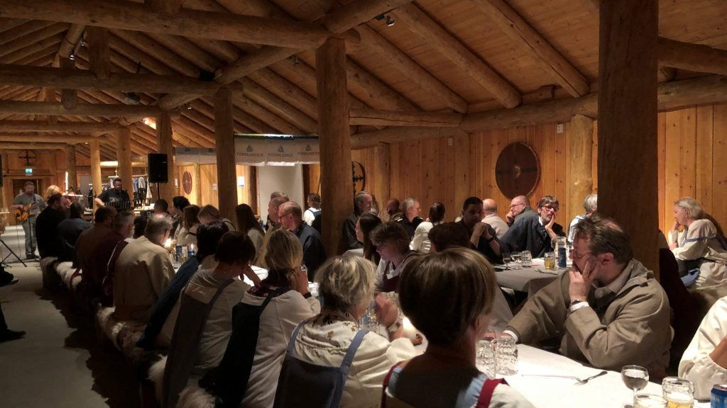 Stor forsamling i langhuset utkledd i vikingdrakter på et langbord med musikkinnslag på et gilde/middagsgruppe