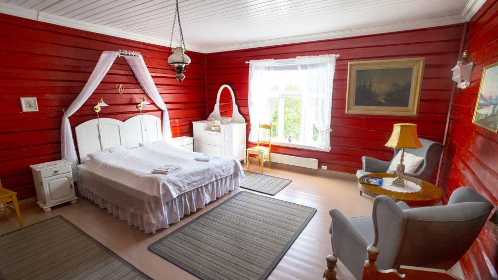 Stort soverom med dobbeltseng, nattbord, stoler, bord og klesskap i eldre stil - med røde vegger