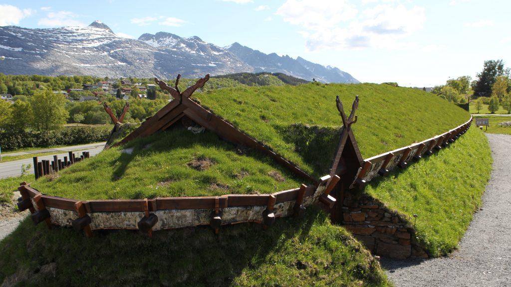 Høvdingsetet med langhuset i front en sommerdag med fjellkjeden De Syv Søstre over mønetaket i bakgrunnen