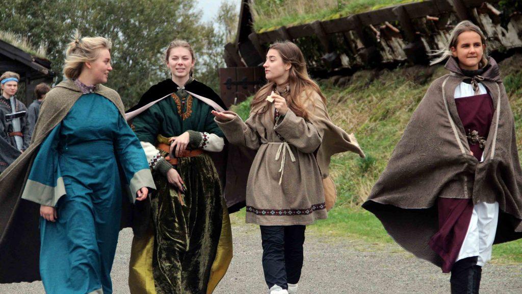 Tre vikingjenter snakker sammen mens de går langs langhuset på høvdingsetet