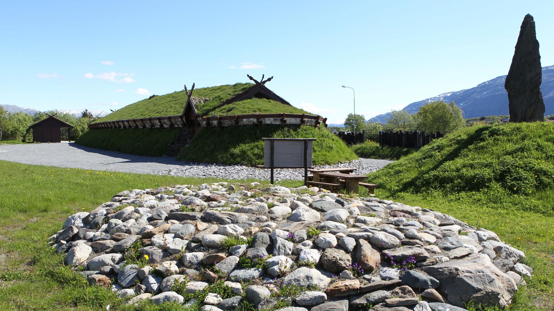 Snødekt bakke og skyfull himmel med en steinbauta på en jordhaug med trappetrinn opp i sentrum av bildet som er reist til øre for vikinghøvdingen Torolv Kveldulvsson