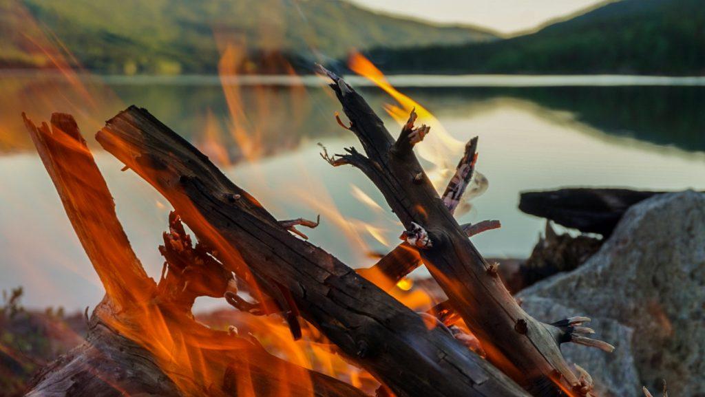 Flammer i bål foran fiskevann