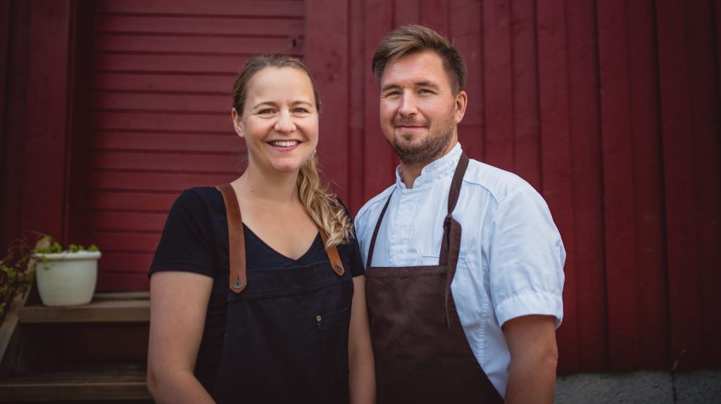 Vertskapet Elise og Marius i forklær foran rød bygning