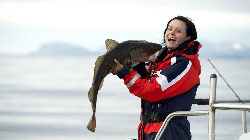 Glad jente som har fått en torsk