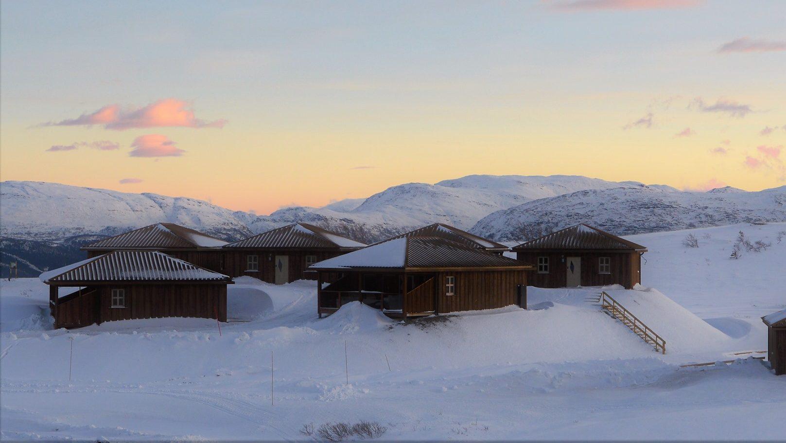Utleiehytter om vinteren med fjell i bakgrunn
