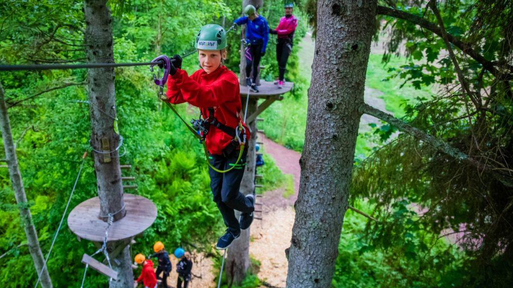 Barn sikret med klatreutstyr som balanserer på stram line høyt oppe i et tre