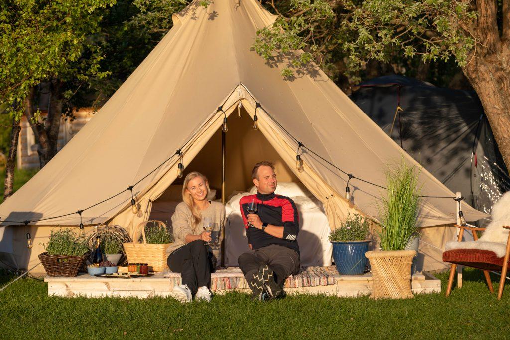 Par som sitter med et glass vin og mat på platt foran glampingtelt