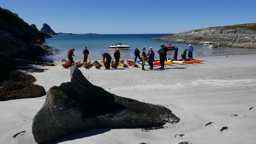 Gruppe kajakkpadlere på sandstrand