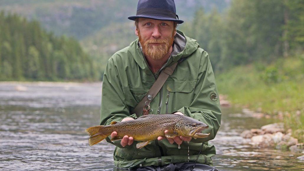 Glad fisker i elva med ørret