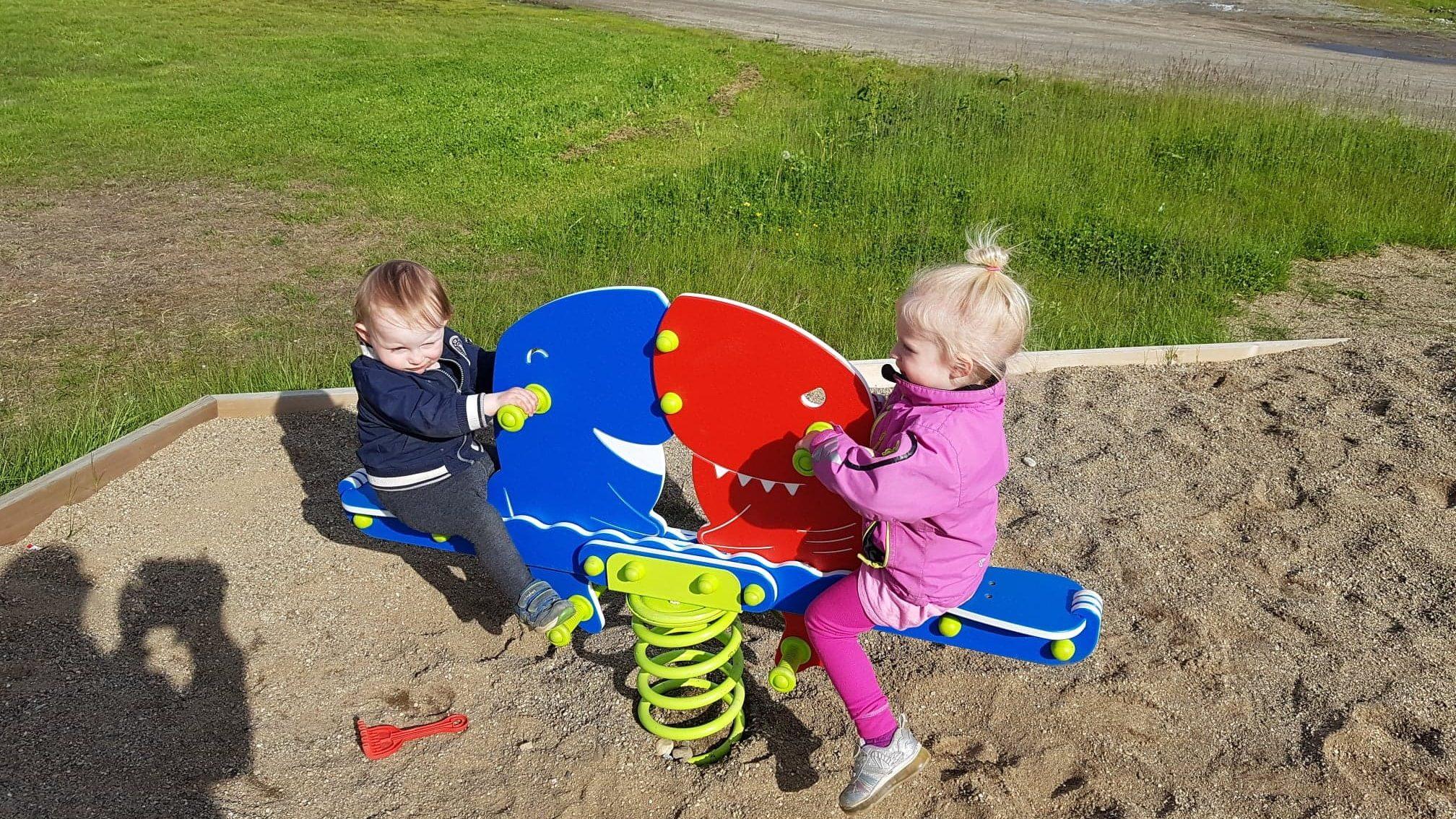 To barn som leker på vippedyr på lekeplass