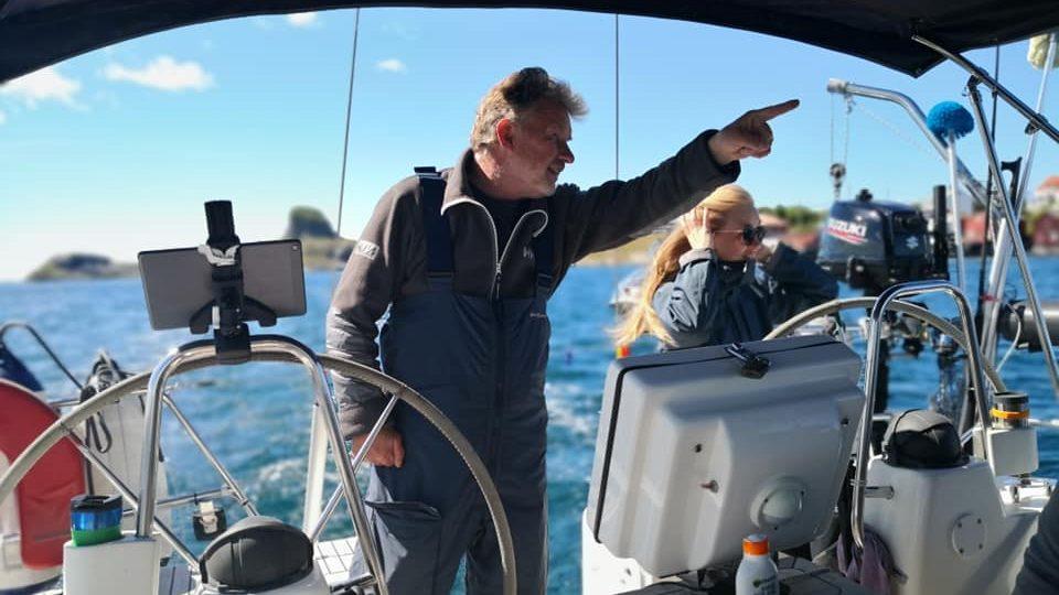 Kaptein peker på noe for passasjer om bord i seilbåt