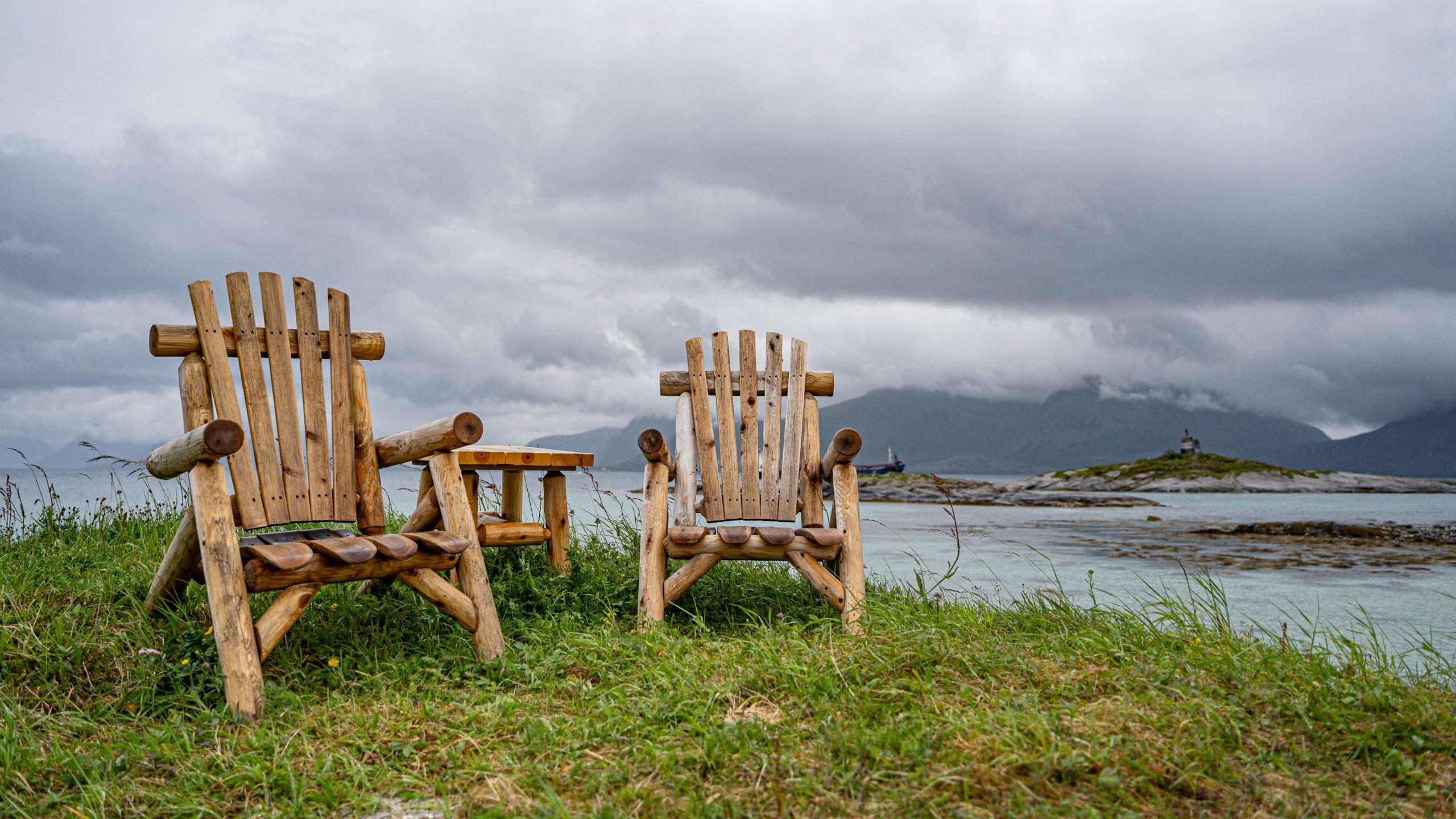 To trestoler med bord mellom som står på gress ved havkanten