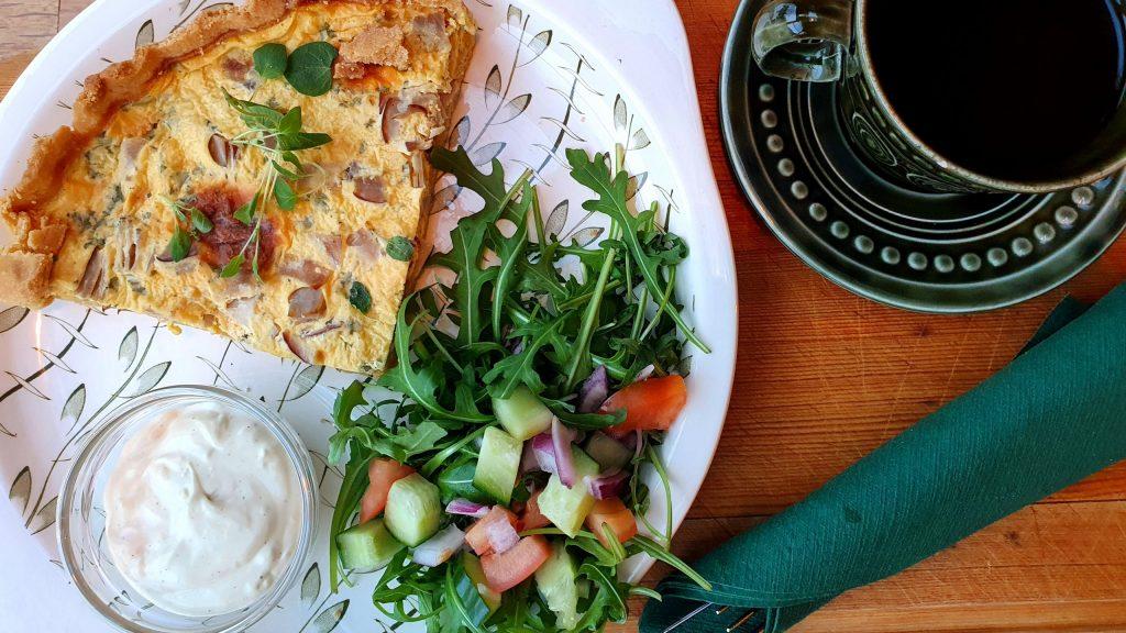 Tallerken med pai, salat og dressing i skål. Kaffekopp og bestikk.