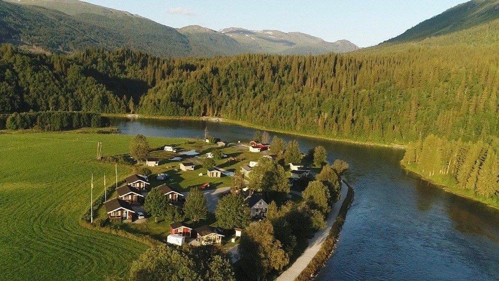 Korgen Camping med elva Røssåga rennende rundt. Skog og fjell i bakgrunn.