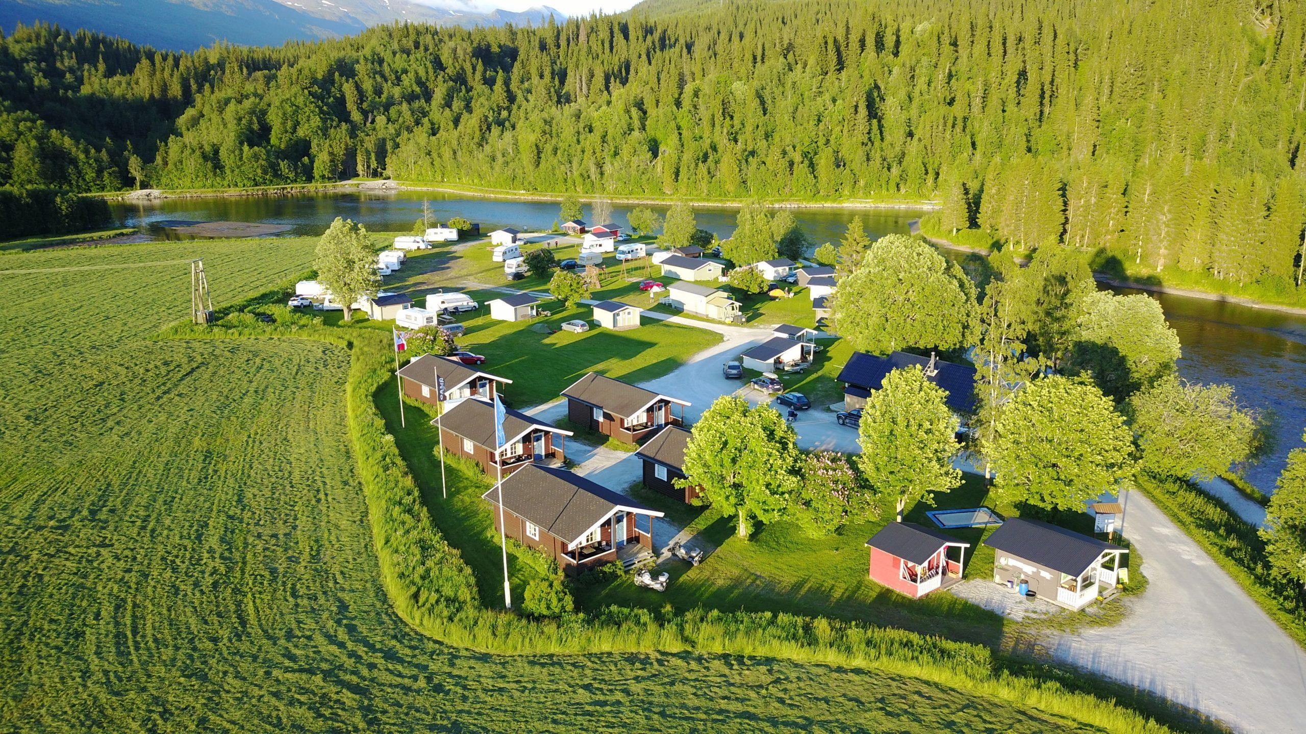 Oversiktsbilde av campingen med elva Røssåga rennende ved siden av