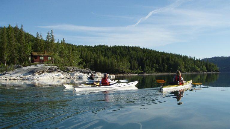 Kajakker på rekke og rad langs land med padlerne som har pause i bakgrunn