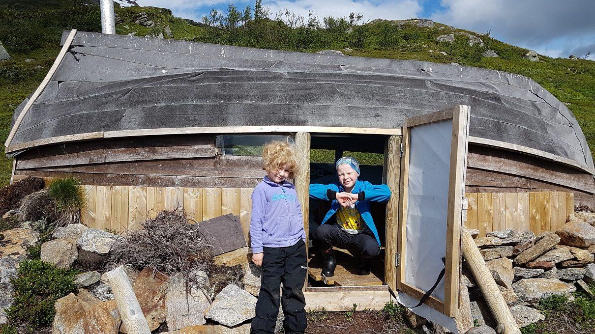 To barn ved en liten hytte laget av en båt