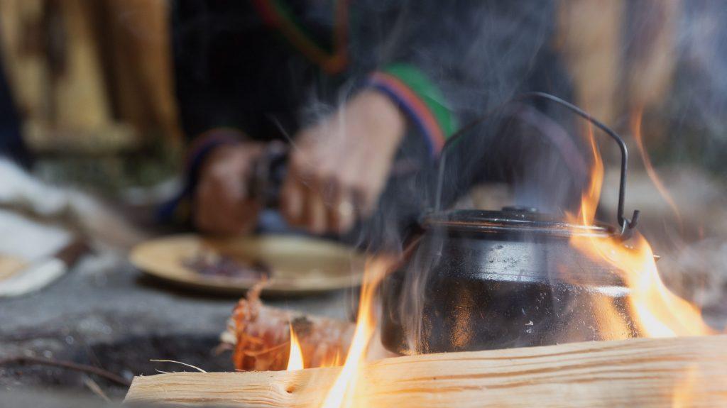 Bål med kaffekjele og person i bakgrunn i samisk drakt som skjærer kjøtt