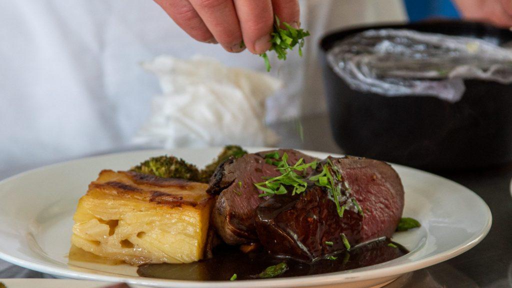Kjøtt i skiver servert på tallerken med potetterte, broccoli, saus og urter