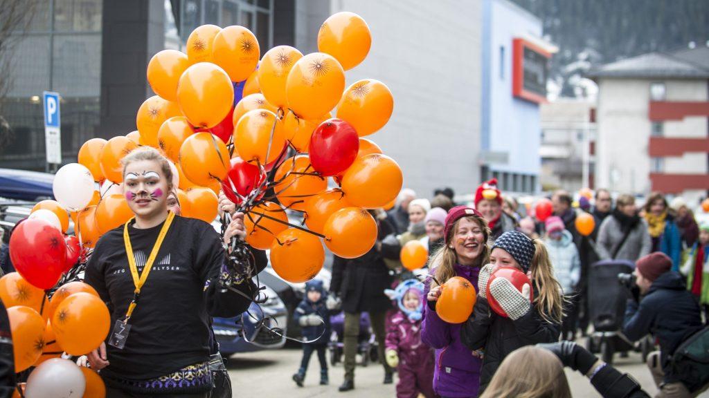 Mennesker ute i gaten med ansiktsmaling og ballonger