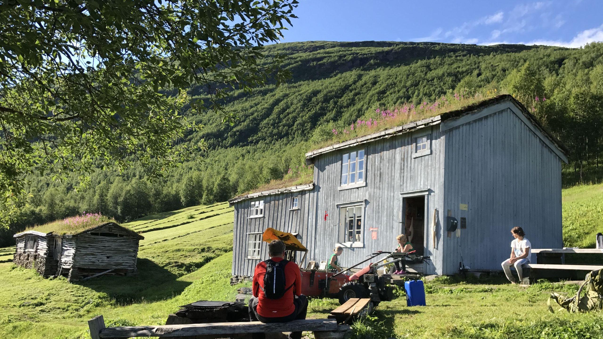 Folk som sitter ute ved gamle bygninger på Bredek fjellgård