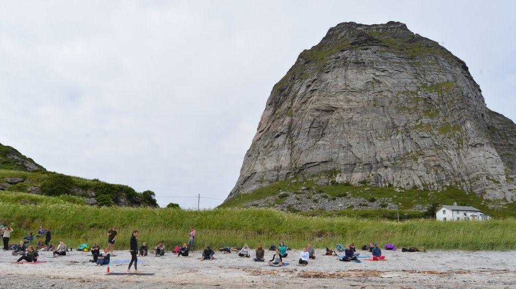 Gruppe som utfører yoga på sandstrand med fjellet Trænstaven i bakgrunn