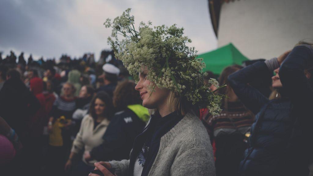 Festivaldeltager med stor blomsterkrans på hodet. Flere folk i bakgrunn.