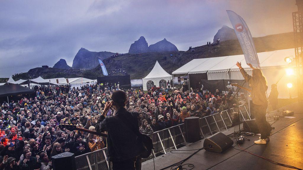 Girl in red på scenen foran publikum med øya Sanna i bakgrunn